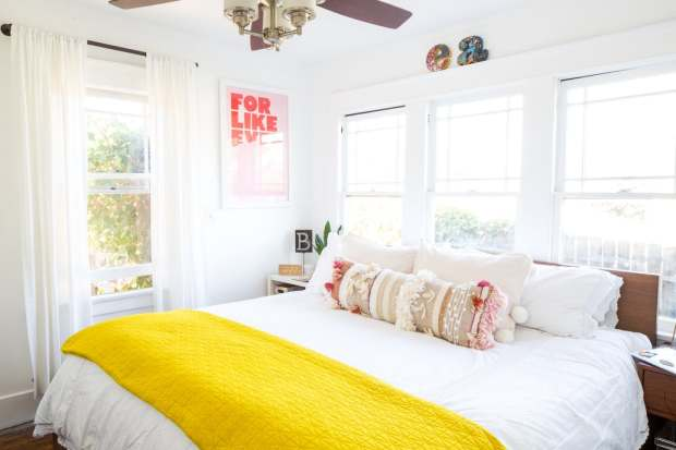 A bedroom with a white bedspread and yellow quilt featured on an Apartment Therapy home tour.