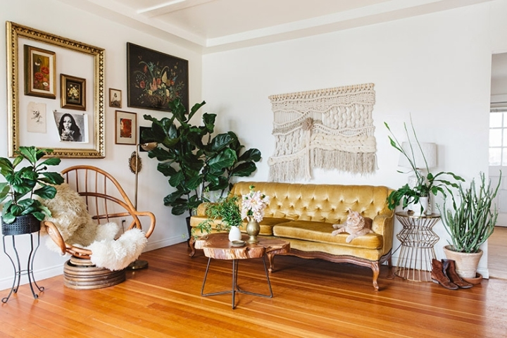 A living room with white walls, a woven macrame wall hanging, a vintage yellow tufted sofa, and a rattan chair and artwork