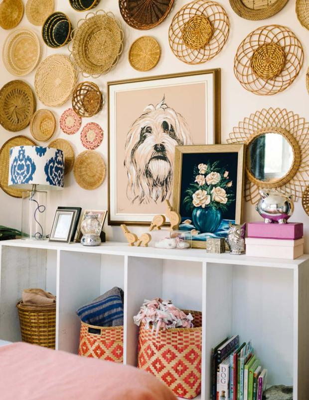A white open shelf cabinet with baskets full of blankets inside and a collection of round rattan baskets on the wall and a large painting of a dog and small painting of flowers propped on top.