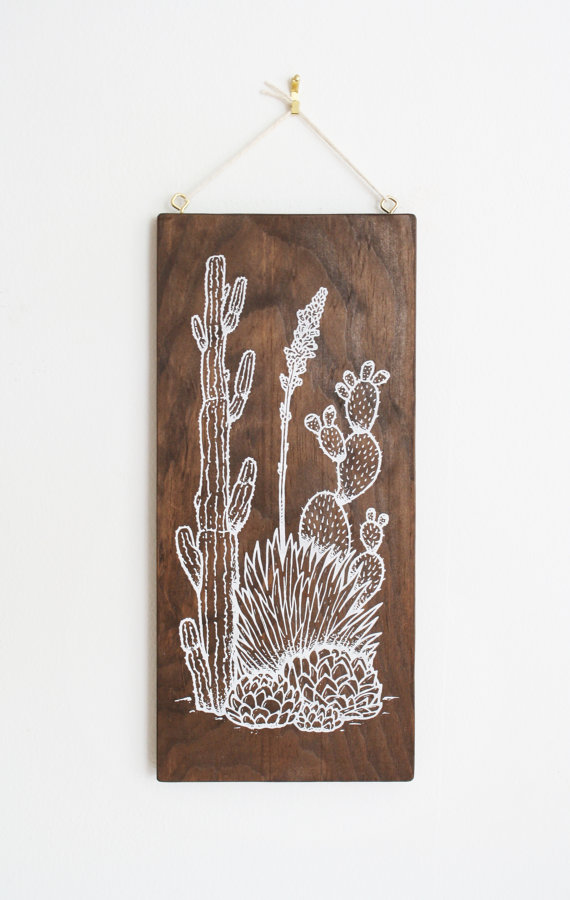 a wood plaque with a cactus illustration in white