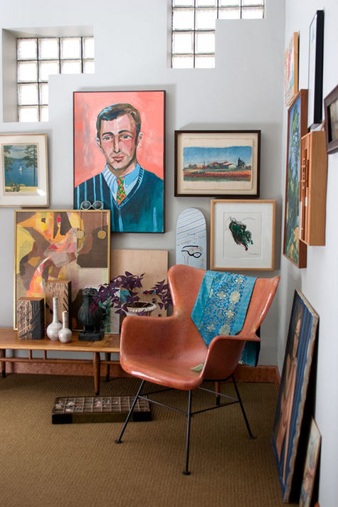 a corner with a molded plastic chair and a gallery wall of vintage artwork