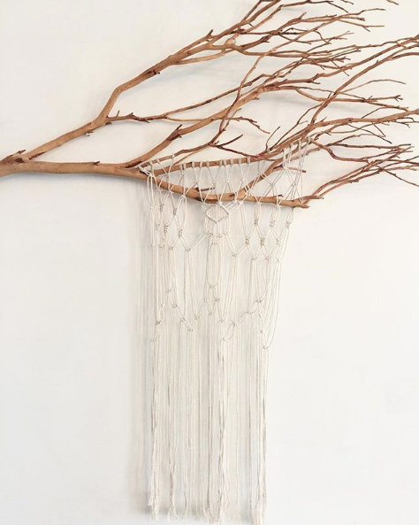a tree branch on a white wall with white macrame hanging from it