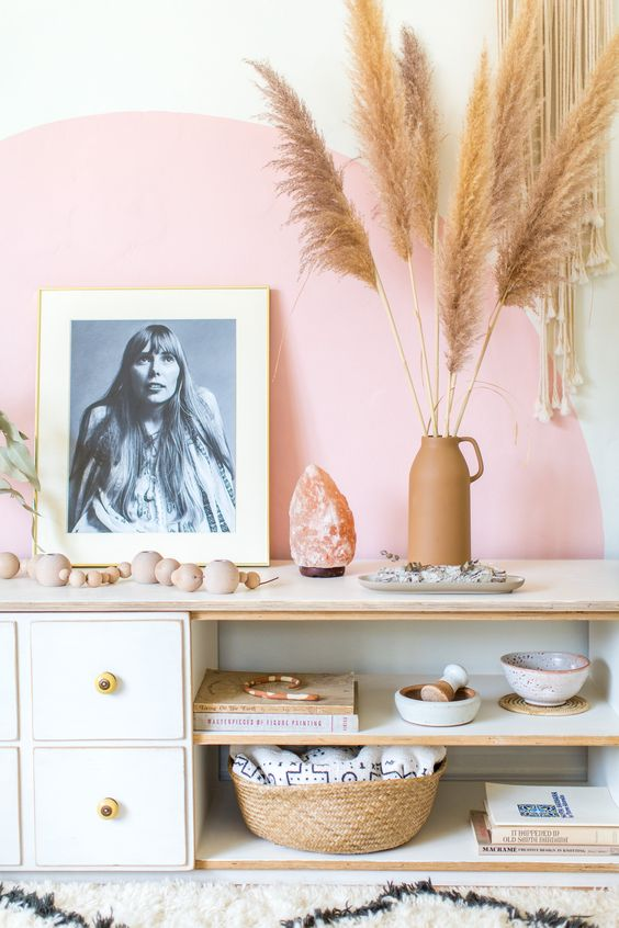 a vignette of a white wall with a pink half moon painted accent, with a white low cabinet and shelves, and a black and white photo propped on top, a salt stone light, clay vase with dried fronds, and a collection of ceramic dishes, a basket, and wooden beads on the shelves.