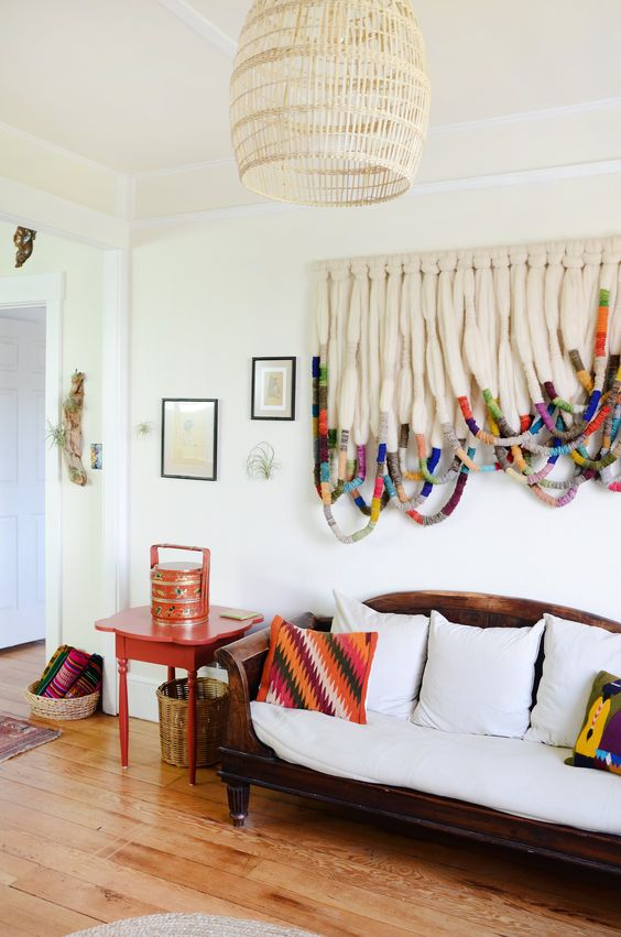 a white walled room with a vintage wooden and white cushioned sofa, colorful pillows, a hanging rattan pendant, and a rope wall hanging with colorful rope pieces woven around each loop toward the bottom