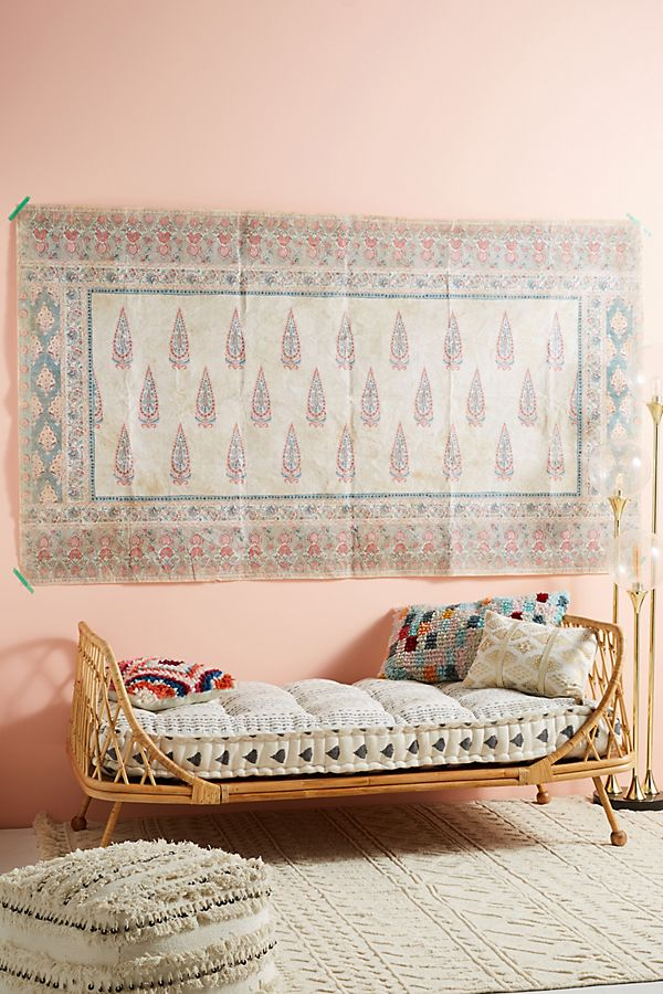an Anthropologie rattan daybed against a pink wall with a pink, blue, and cream colored tapestry hanging above