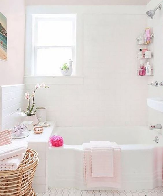 a light pink and white bathroom with a white tub, orchid in the corner, and rattan side table with pink towels folded on top