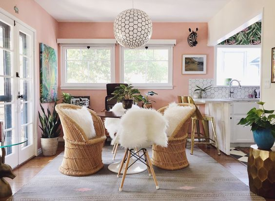 a pink kitchen and dining area with a hanging globe pendant light and woven rattan style seats with sheepskins throws hanging over them