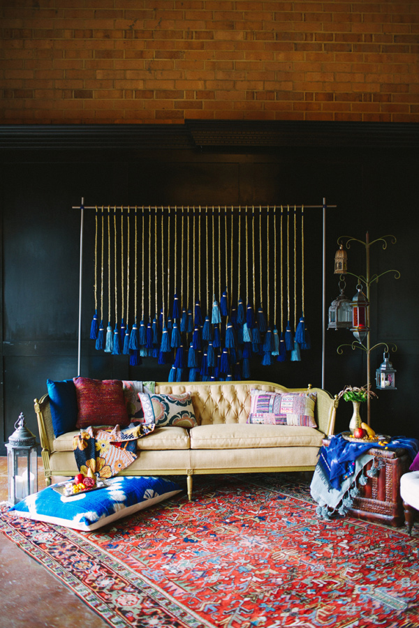 a dark blue wall with a wooden ceiling, with a yellow tufted vintage sofa, red and blue pillows, a Persian rug beneath, and a wall hanging consisting of hanging strands with dip dyed blue tassels at the ends