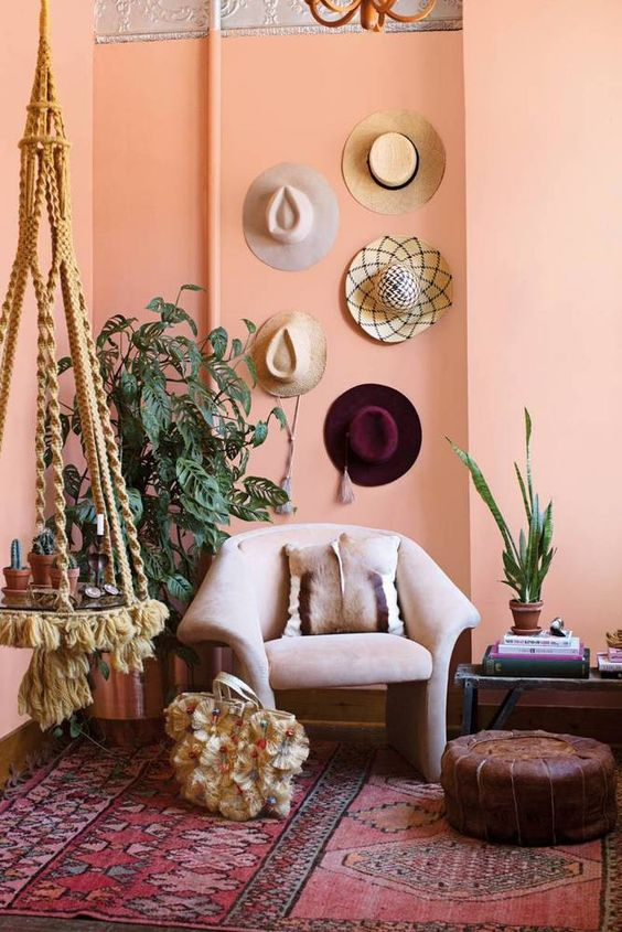 a pink walled room with hanging hats, a club chair, persian rug, and a macrame hanging table with plants on it
