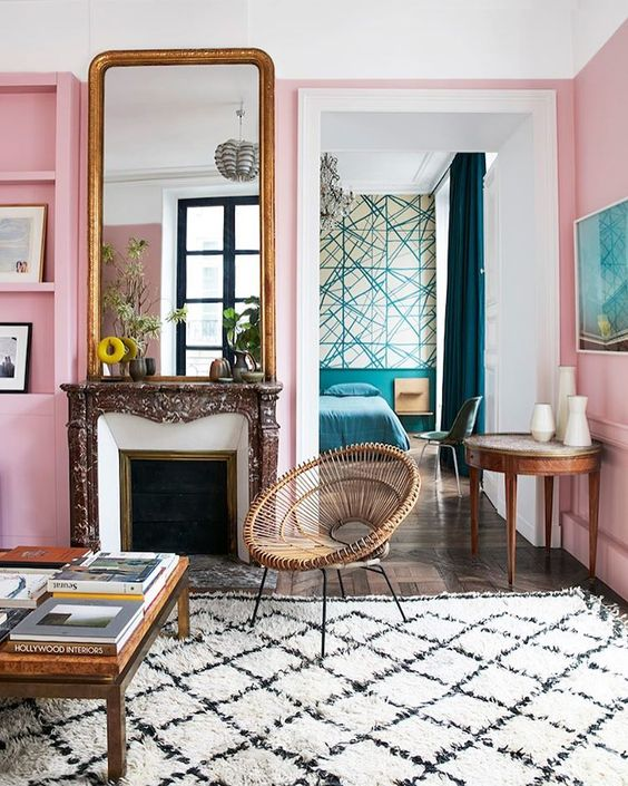 a pink room wit ha fireplace and tall Louis Phillipe mirror on top, a white and black criss cross moroccan area rug below, a round rattan chair, and a large coffee table with several art books